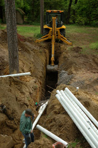An open drainage trench with men installing 4-inch perforated PVC pipes.