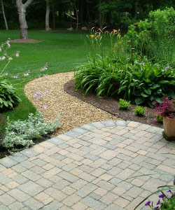 A well-landscaped yard featuring gravel and paving stone walkways.