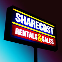 A photo of the Sharecost sign at night.