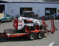 Our tandem-axle trailer, holding a skid-steer loader, being towed by a 3/4 tonne truck.